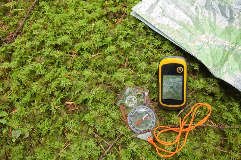 A GPS, a compass and a map on the ground