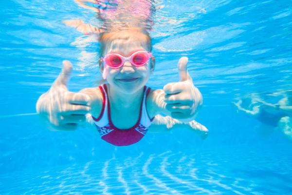 Girl wearing pink water glasses giving thumbs up underwater