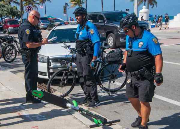 Police officers investigate an electric motor scooter accident on the street by the beach in Ft Lauderdale, Florida.