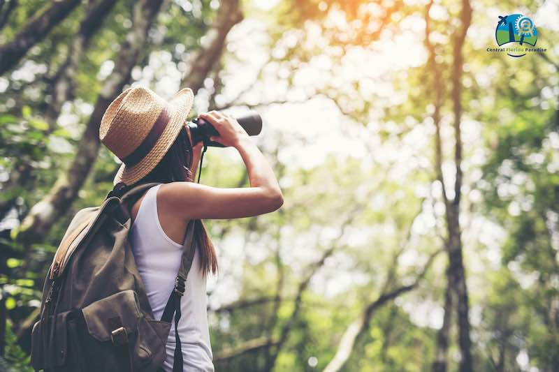 Young Lady With a Backpack looking through a binocular