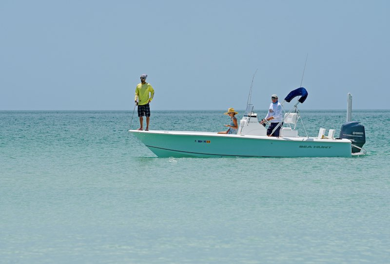 People fishing in open water from a white boat