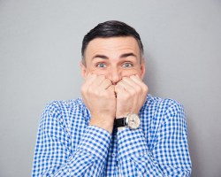 Worried man in front of a grey background