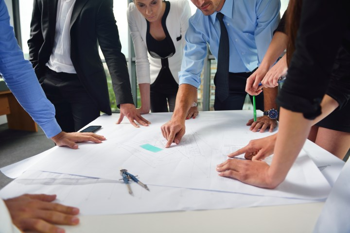 people meeting around plans on a table