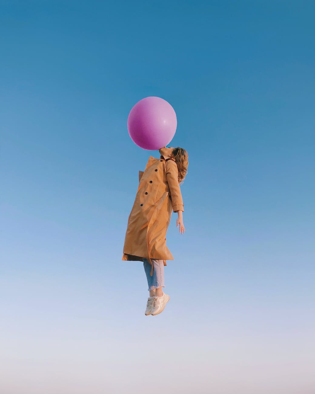 young female blowing huge balloon in sky