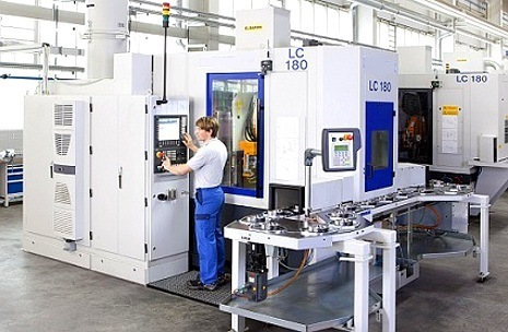 a man standing in front of a large manufacturing CNC machine used to shape metal