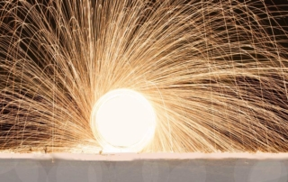 an image of a circular metal saw it's completely engulfed in sparks and they are raining down creating like the thousands of spokes of a wheel