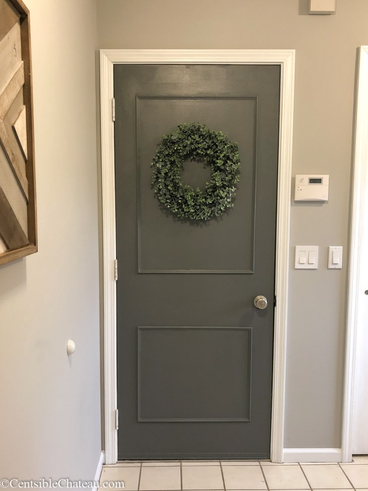 Farmhouse laundry room finished door with trim, paint and wreath