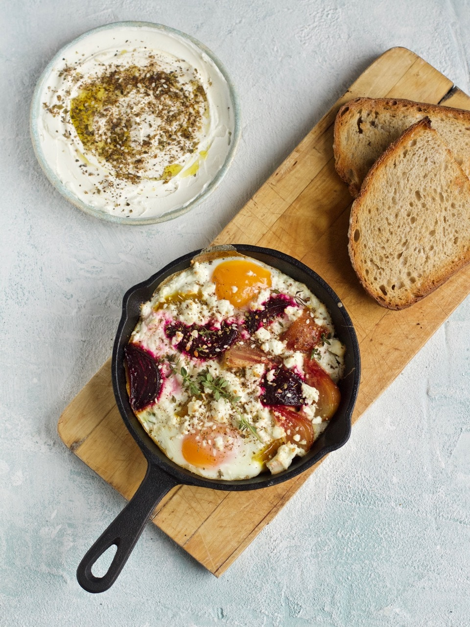 Individual cast iron pan baked eggs with beetroot, feta and thyme