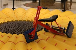 Kids could ride this trike with uneven square wheels and take it for a spin along this bumpy surface