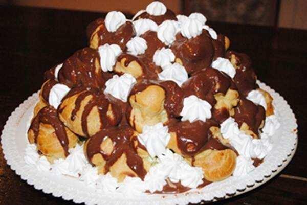 Profiteroles di cioccolato e panna ripieni di crema di pistacchio
