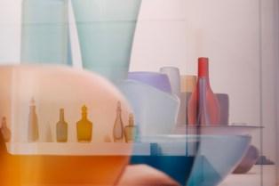 Bunte Gläser und Vasen spiegeln sich mehrfach im Glas