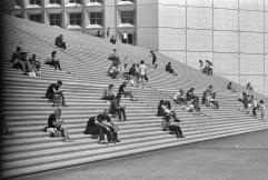 Menschen machen Mittagspause auf der Treppe des Grande Arche II
