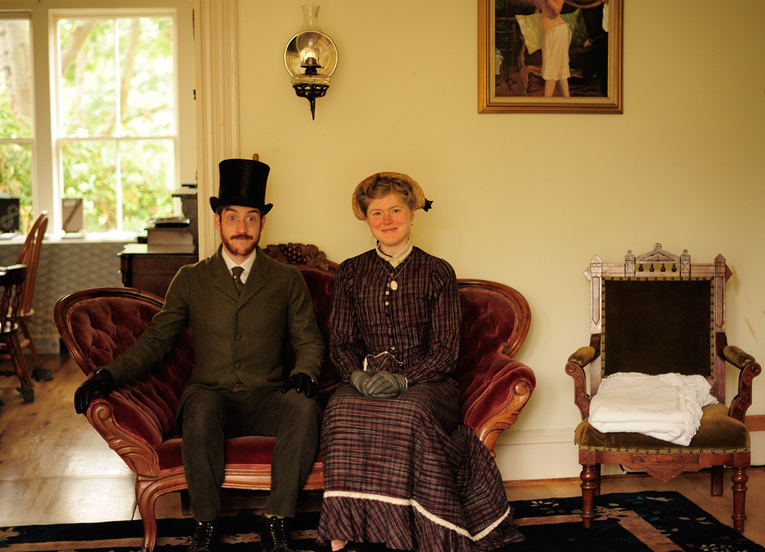 The Chrismans sit in their parlor on a couch from the 1890s. A gas lantern is installed on the wall above them. (Photo courtesy Estar Hyo-Gyung Choi, Mary Studio, via ThisVictorianLife.com)