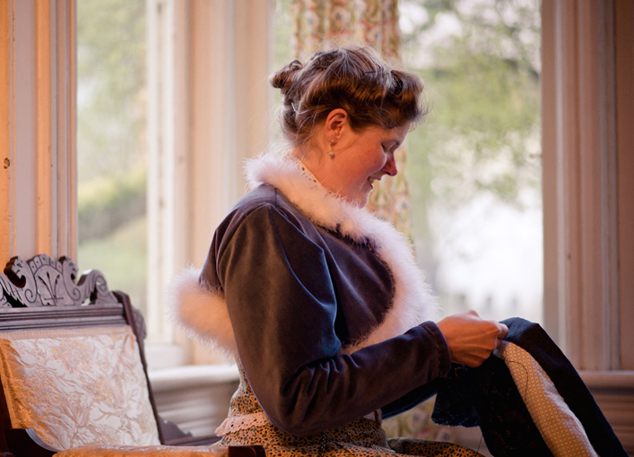 Sarah hand-sews her clothing in an 1880s Eastlake Gothic style chair in her parlor. She wears a cotton velvet bolero jacket with down trim she based on a painting from the period. (Photo courtesy Estar Hyo-Gyung Choi, Mary Studio, via ThisVictorianLife.com)