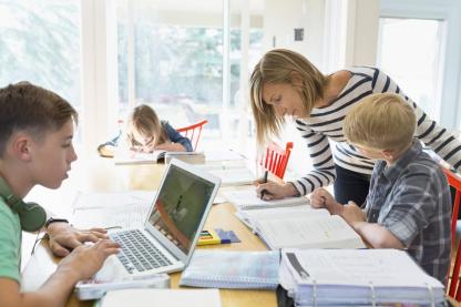 Mother with kids studying at dining table