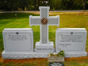 Custom designed granite double headstone with cross and bronze emblem