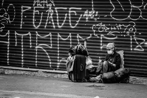 unrecognizable tourist in mask with suitcase near graffiti wall