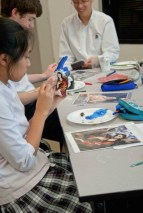 Student painting a destroyed El Greco painting onto a plaster cast of her hand.