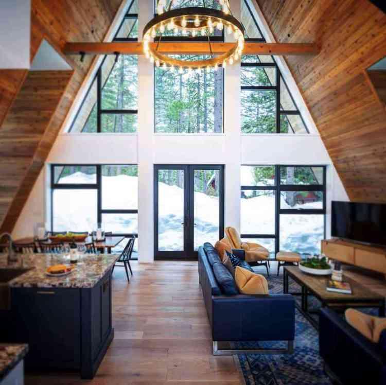 chalé de topo alto que contrastas grandes janelas em parede branca com interior de madeira na cor natural.