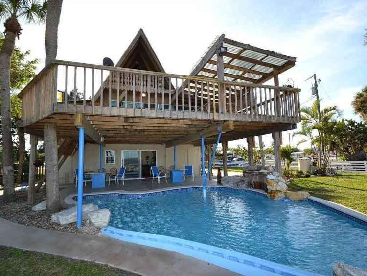chalé com deck construído acima da piscina.
