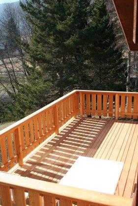 Le grand balcon, disposition sud, avec table et chaises d'extérieurs. L'escalier au jardin est protégé par un barrière.
