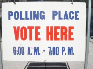 "A sign from a polling booth, it says ""Polling place, vote here 6:00am-7:00pm""."