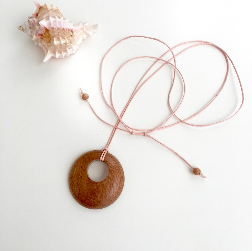 Round Rosewood pendant on pale pink cotton cord.