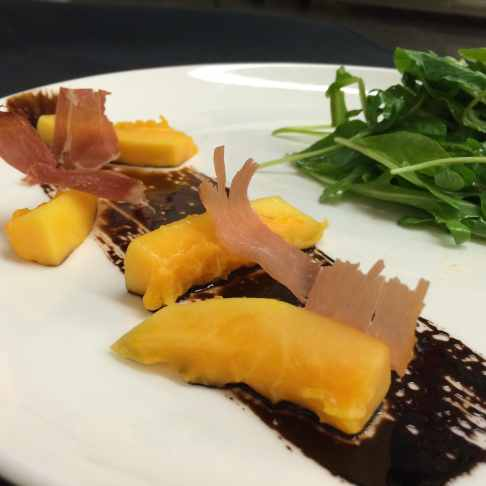 Papaya bitter green salad with balsamic streak and prosciutto