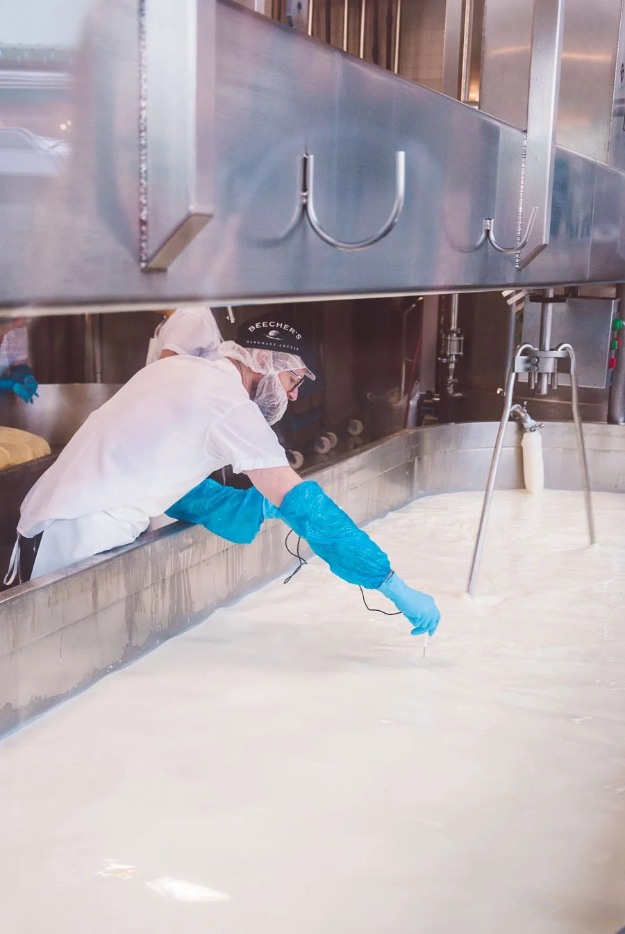A Beecher's cheesemaker leaning over to take the temperature of a large tub of milk