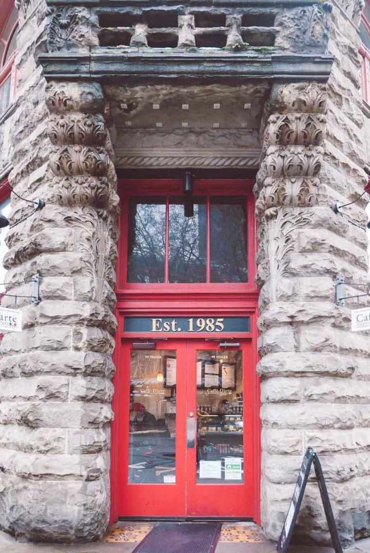 Storefront image of Caffe D'Atre's two red doors surrounded by brick.