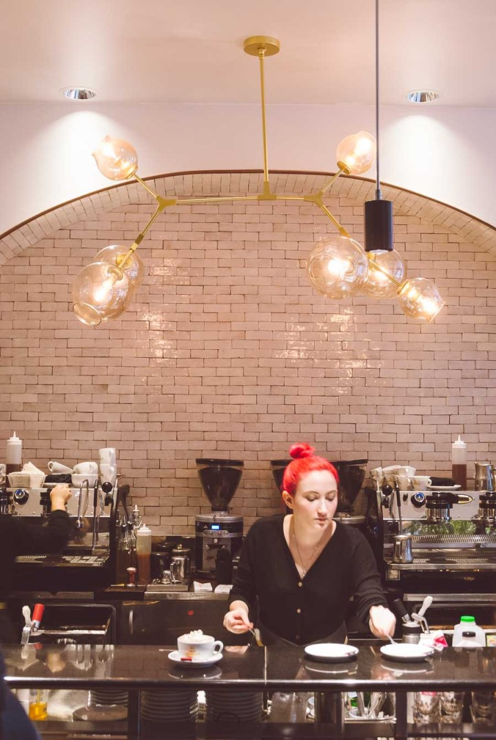 Barista with red hair serving coffee at Caffe Umbria