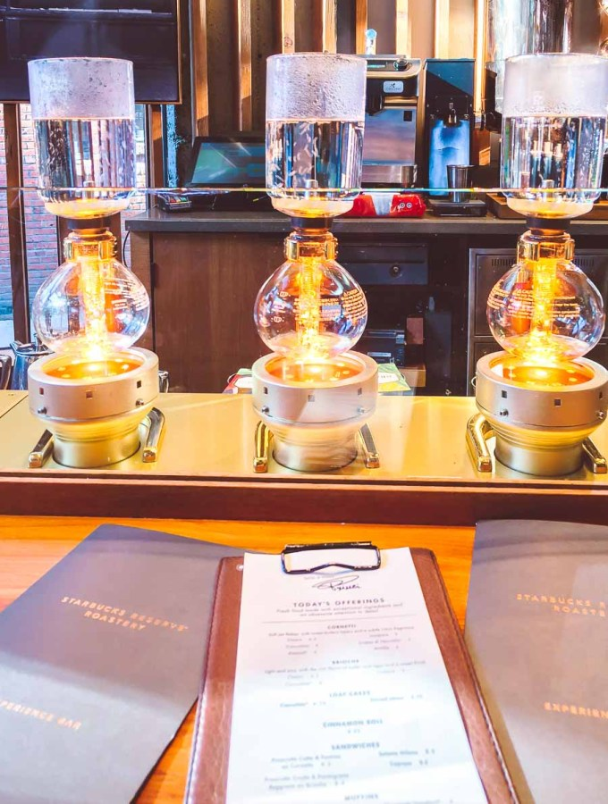 Three siphon coffee machines brewing with Starbucks Experience Bar menus on the table