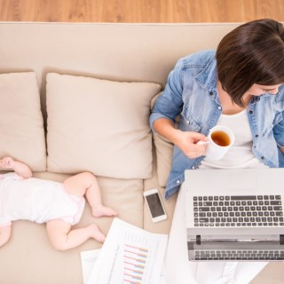mother working on laptop with baby