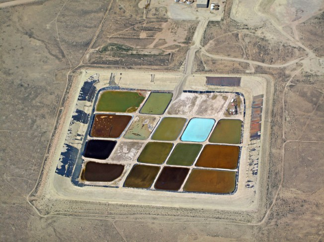 "Gelling agents, acids, friction reducers, surfactants and many other chemicals are pumped into the ground to break up rock formations and release natural gas. Many of these chemicals are known carcinogens and volatile organic compounds. After returning to the surface, the ""produced"" water is placed in evaporation ponds and dispersed into the air. Fracking fluid is exempt from the Safe Drinking Water Act and drilling companies are not required to disclose all the chemicals they use. Credit: EcoFlight"