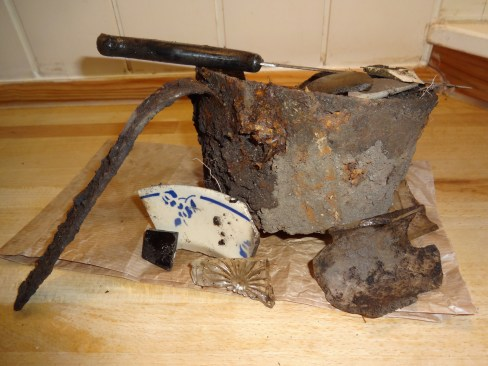 The stuff from under the tree root. Note the pickaxe hole punctured in the side of the pot.
