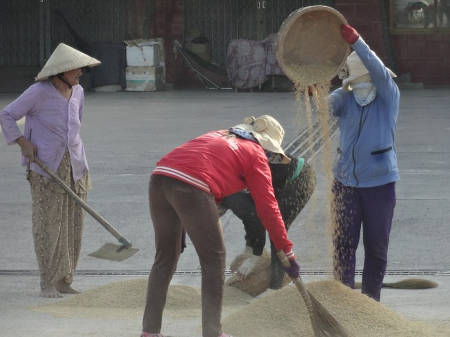 Women separating rice from chaff near a gas station parking lot.