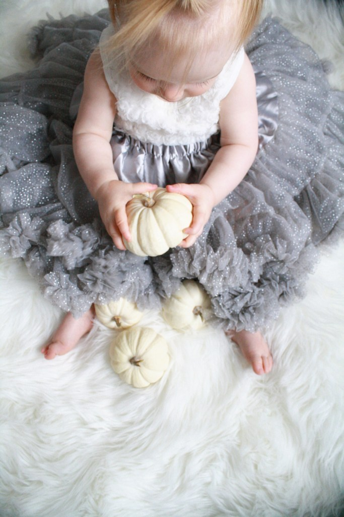 Baby girl with white pumpkins