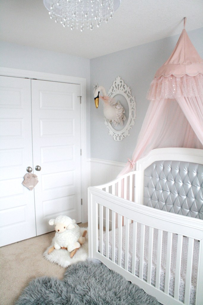Pink and gray nursery for baby girl with silver tufted crib and pink canopy
