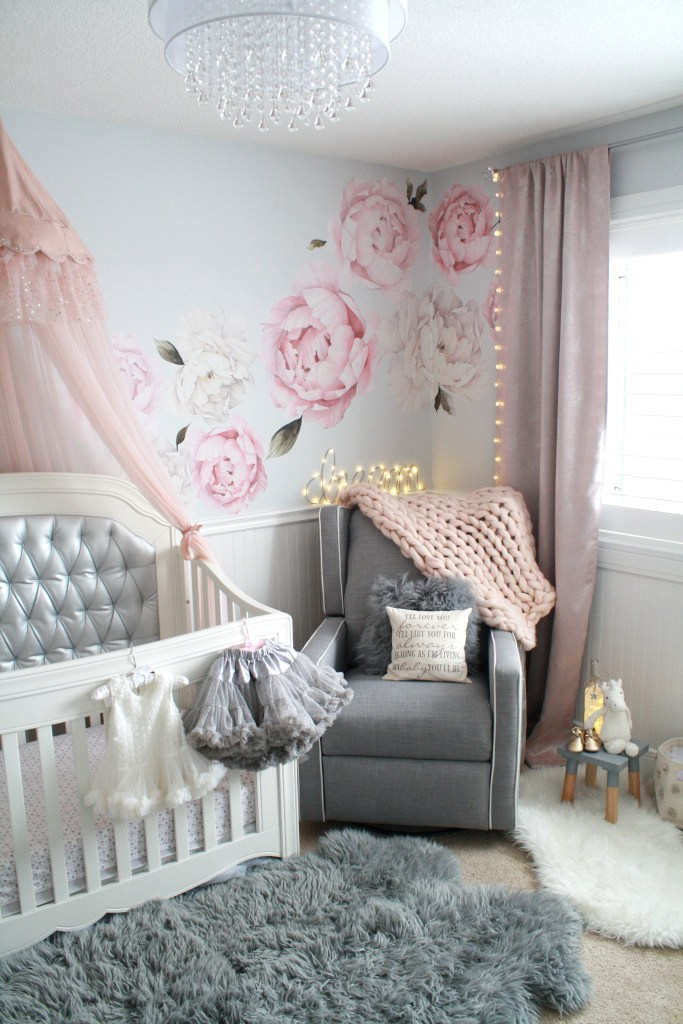 Pink and gray nursery with silver crib, peony decals and sheepskin rug
