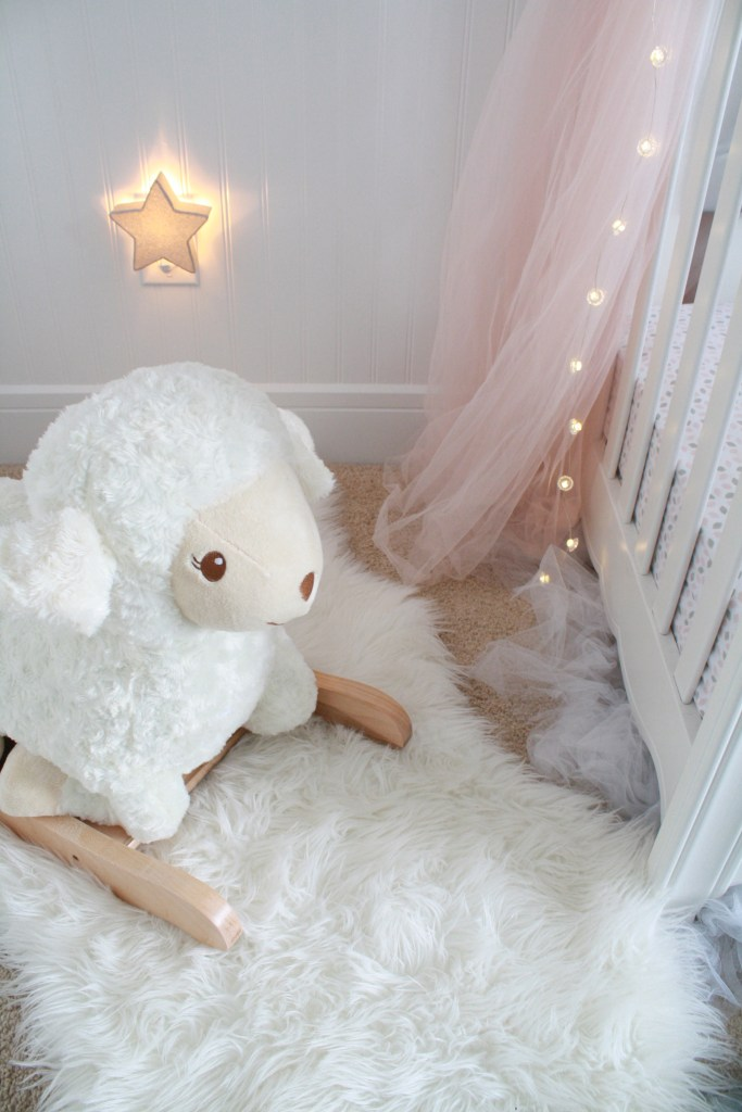 Pink and gray nursery with rocking lamb and star light