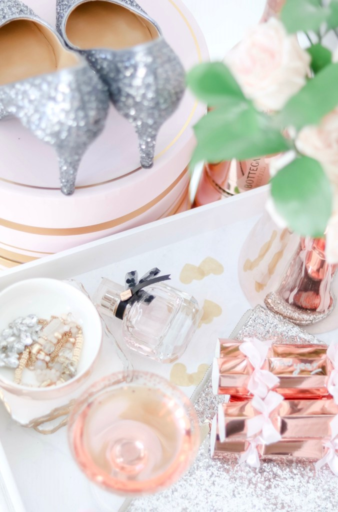 New Year's Eve styled vanity with sparkly heels, sparkling rosé , perfume and fresh roses