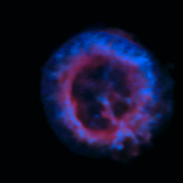 Chandra/ACIS X-ray image of E 0102. The blue and the purple are false-coloured fast-moving highly ionized gases. This forms a lightyears-wide shell around what is thought to be the origin of the supernova. Note the small blue dot south-south-west of the centre, and about midway to the outer ring.