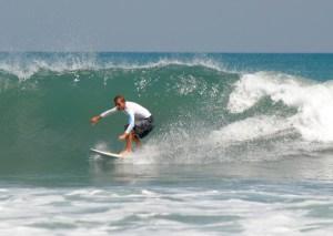 Intermediate surfer catching a wave in Legian, Bali