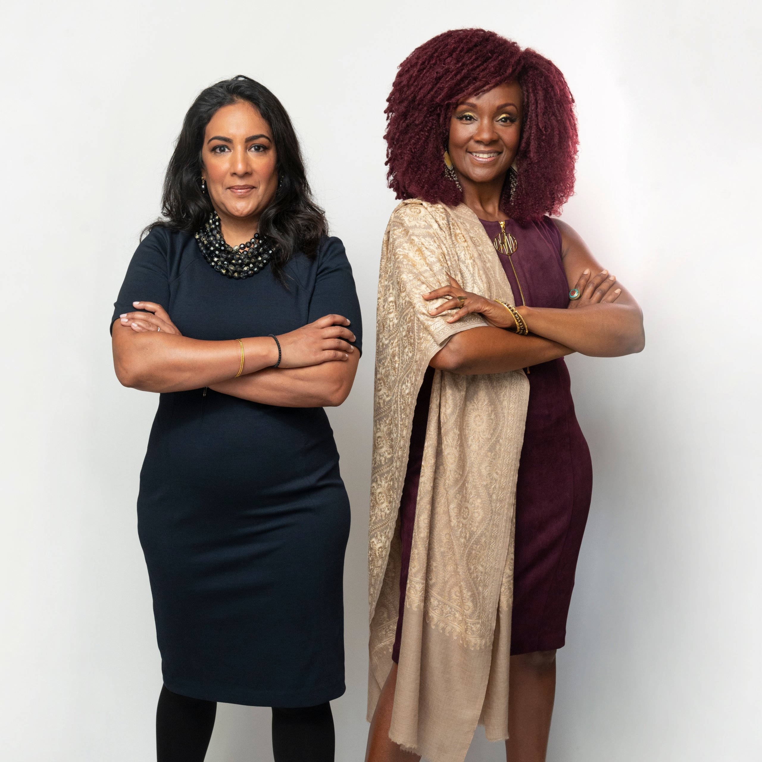 Deepa Purushothaman, an Indian-American woman with black hair and beaded necklace, and Rha Goddess, a Black woman with burgundy hair and gold shawl.