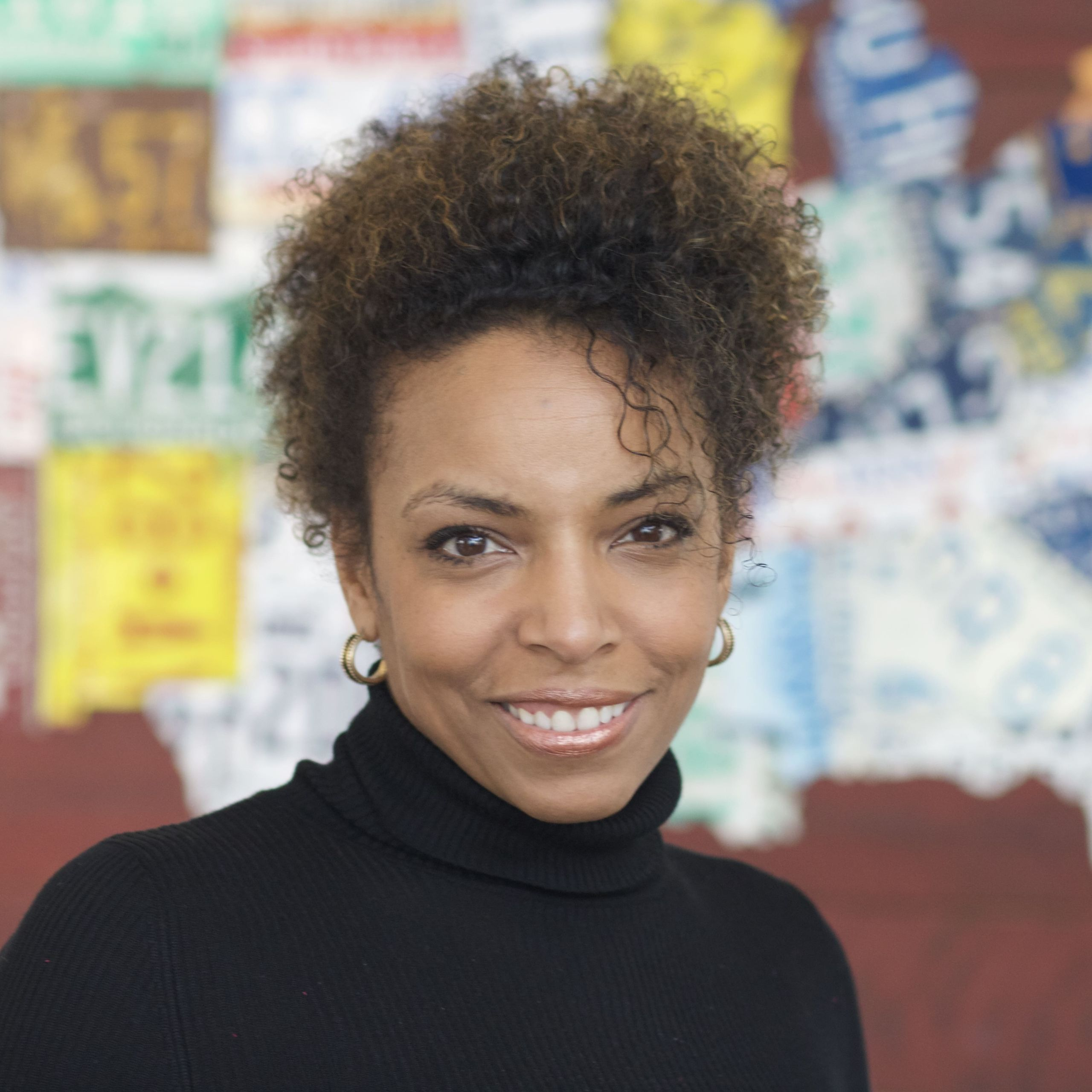 Headshot of Cynthia Overton, a Black woman with natural curly hair swept up and a black turtleneck