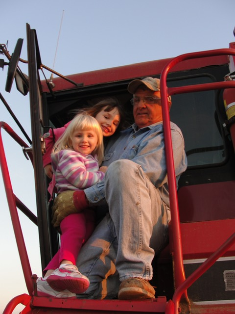 My daughters in the combine with Granddad several years ago
