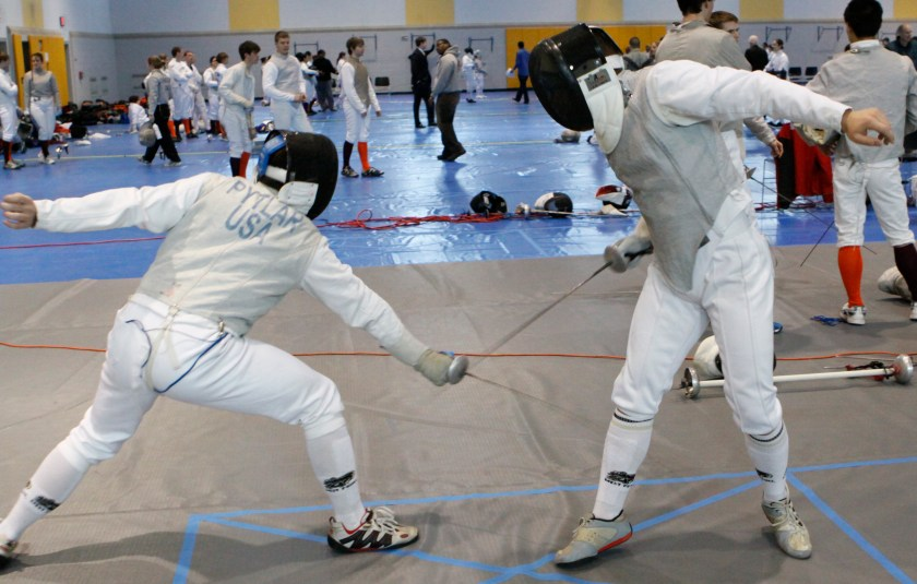 two persons practicing fencing while others watch
