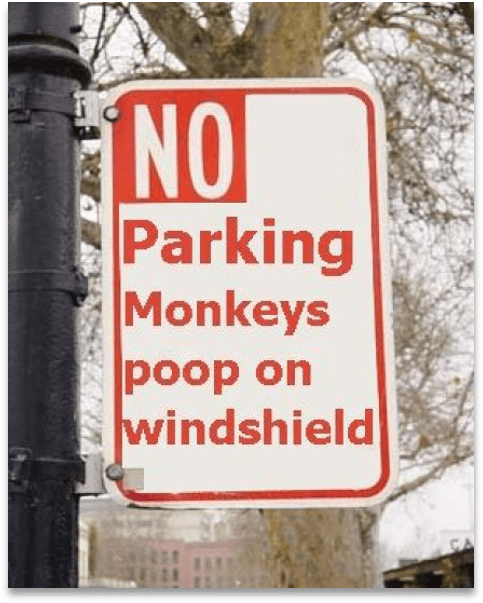 A sign on a pole that says, No parking; Monkeys poop on windshield