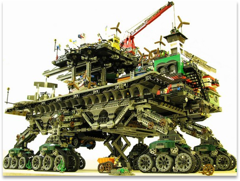 A large lego structure built to travel and containing ongoing construction on its various levels