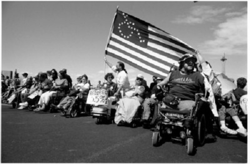 Black and white photo of a line of ADAPT activists in wheelchairs charging up and over a hill. They bear a flag, roughly like the American flag, but with the stars in the form of a wheelchair symbol.